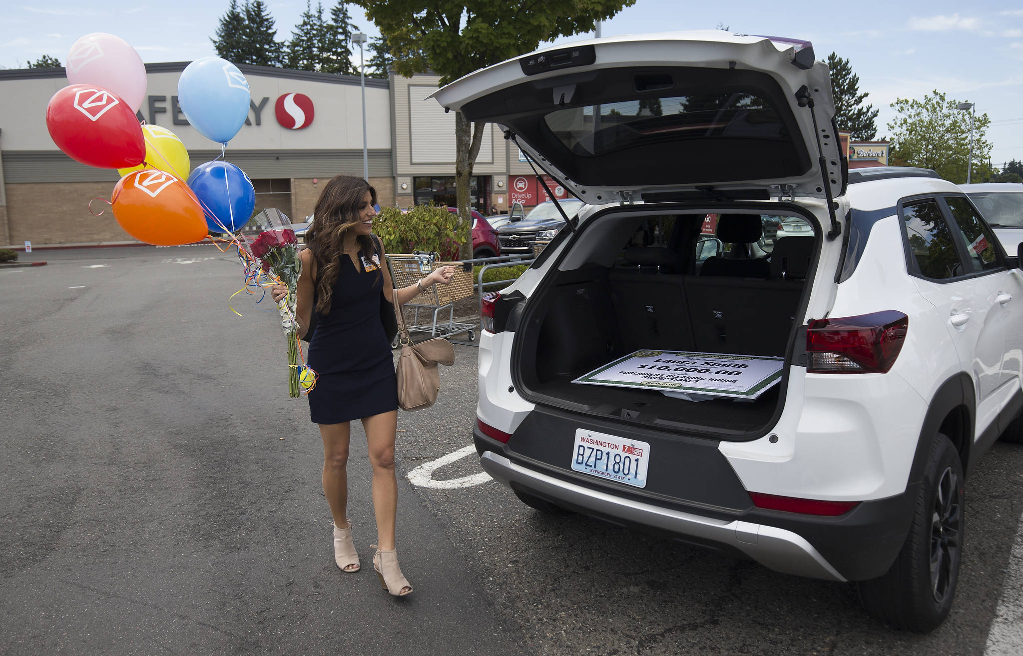 Before every delivery, Danielle Lam with the Prize Patrol from Publishers Clearing House fills balloons and gets flowers for the winner. (Andy Bronson / The Herald)