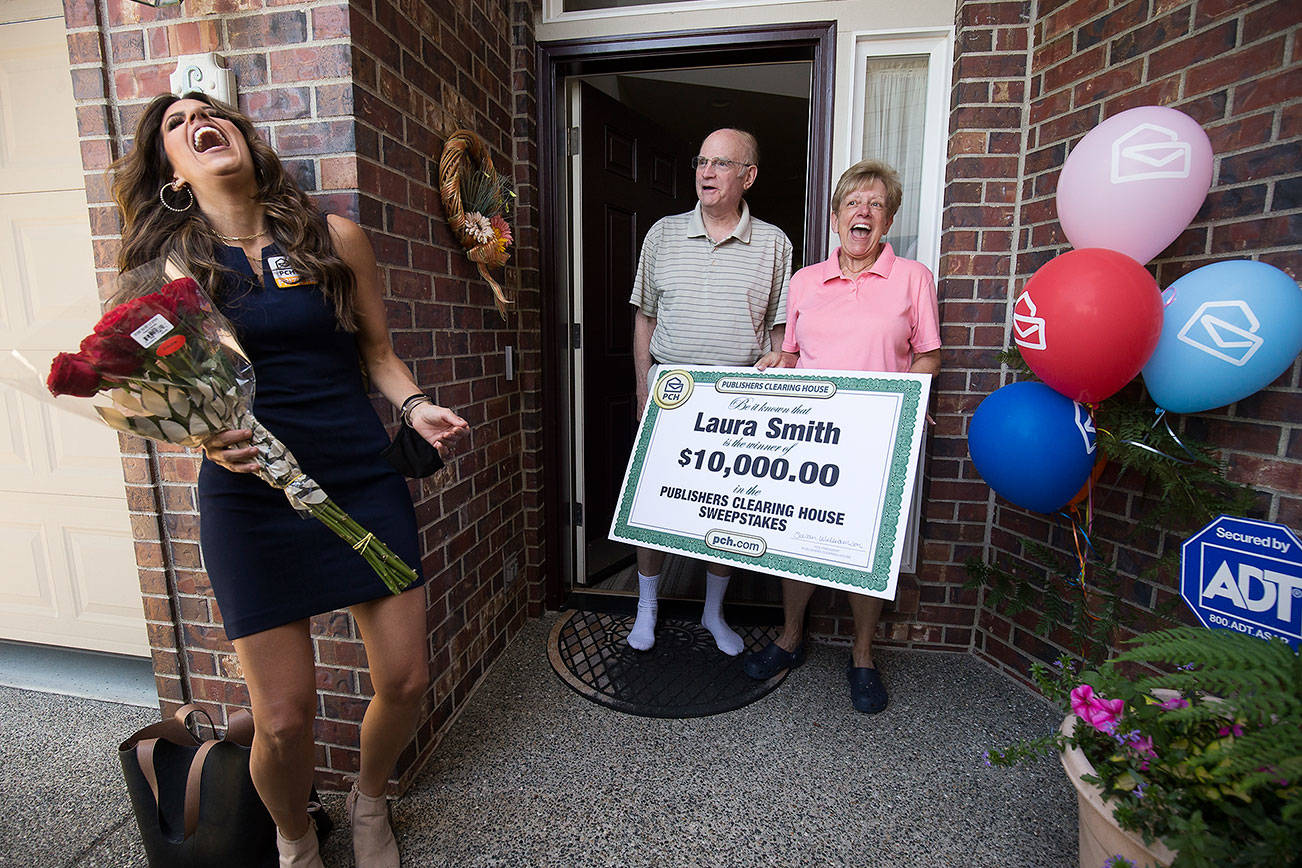 Laura Smith, with husband Tom, makes Danielle Lam laugh after being presented with a check for $10,000 from The Prize Patrol from Publishers Clearing House on Wednesday, July 28, 2021 in Mukilteo, Washington. (Andy Bronson / The Herald)
