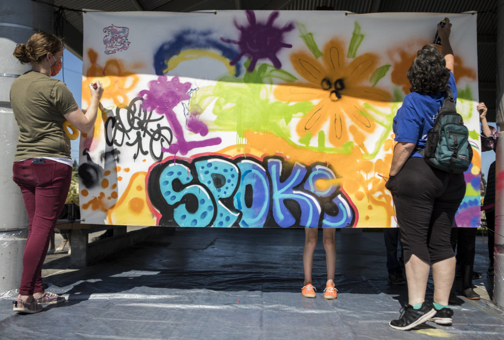People add to a collective spray paint mural hosted by JAG Artworks on Sunday during the Delta Art Experience in Everett. (Olivia Vanni / The Herald)