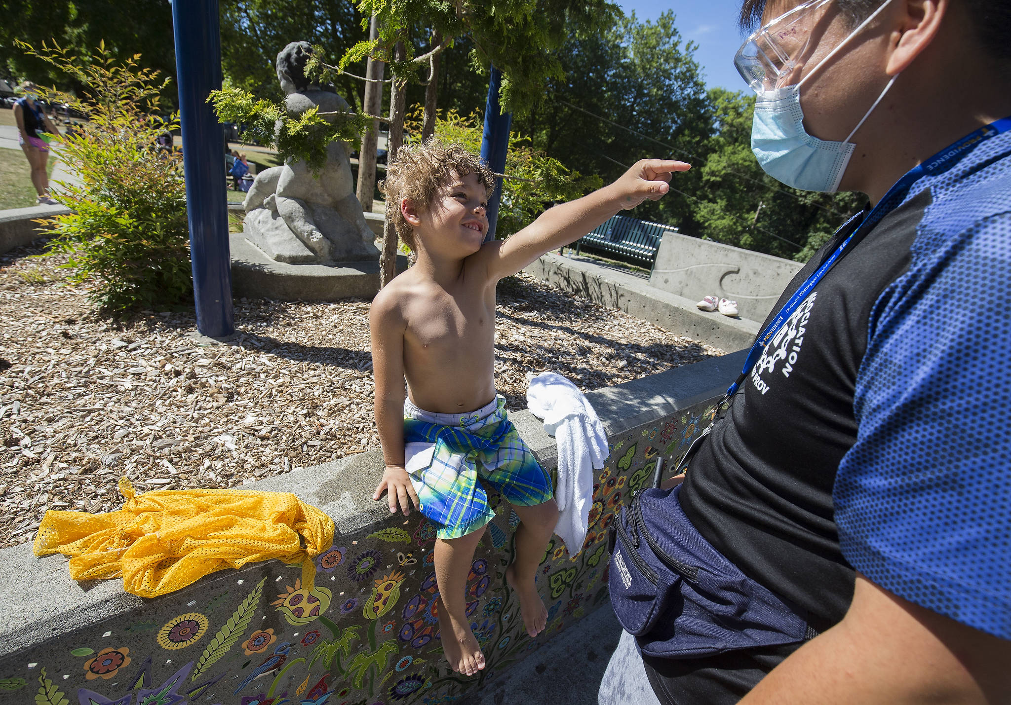 """Soren Williams, 4, points at Quang Pham and says, """"I love you,"""" after drying off from playing in the water at Forest Park in Everett. (Andy Bronson / The Herald)"""