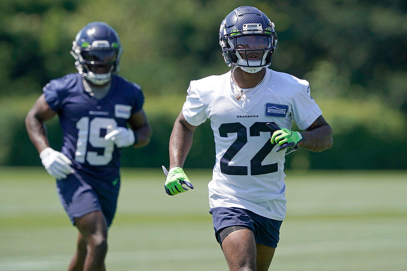 Seattle Seahawks rookie cornerback Tre Brown (22) runs with wide receiver Penny Hart (19) during NFL football practice Thursday, July 29, 2021, in Renton, Wash. (AP Photo/Ted S. Warren)