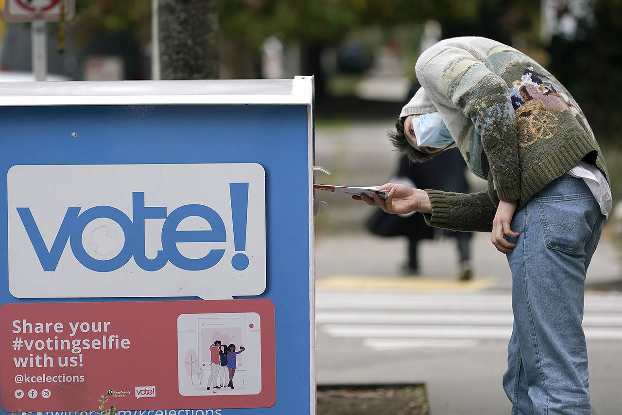 A voter turns peers into the opening of a ballot drop box before placing his ballot inside it in Seattle in October, 2020. (Elaine Thompson / Associated Press file photo)