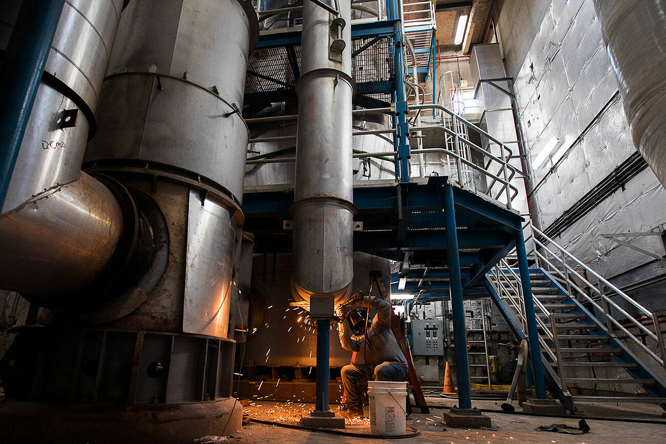 A worker disassembles a fluidized bed incinerator at the Edmonds Wastewater Treatment Plant on Thursday, Sept. 16, 2021 in Edmonds, Wa. (Olivia Vanni / The Herald)