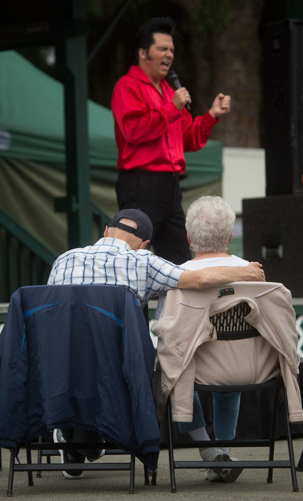 A couple watches Danny Vernon, Illusion of Elvis Presley tribute impersonator, perform at the Evergreen State Fair on Monday in Monroe. (Andy Bronson / The Herald)