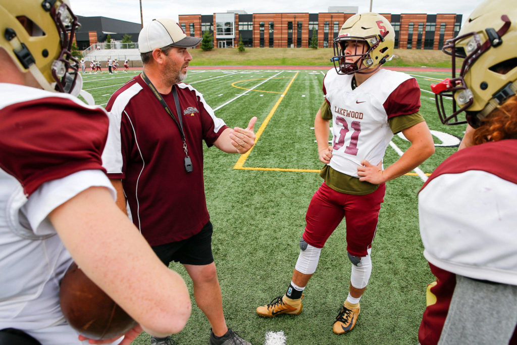 Dan Teeter, head coach, talks with Justice Taylor during a quarterback huddle in practice Tuesday afternoon at Lakewood High School in Arlington. (Kevin Clark / The Herald)