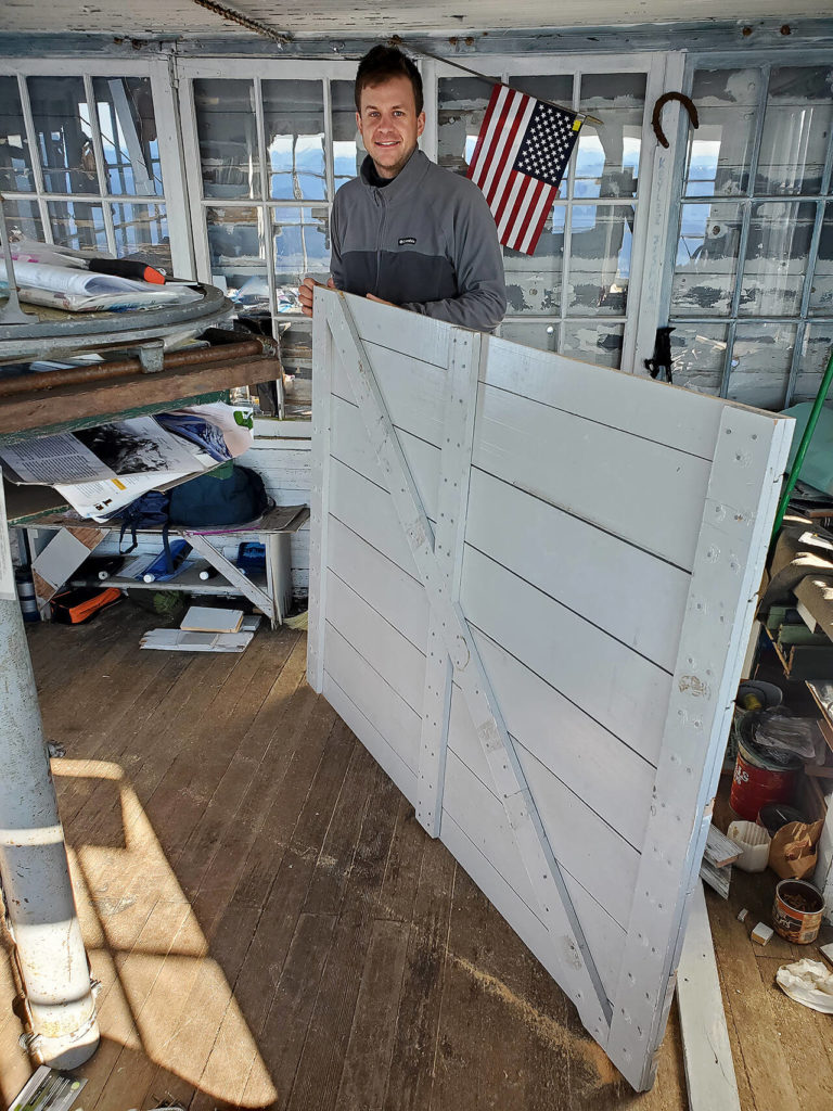 Zach Schrempp readies a new shutter to be installed at Three Fingers Lookout. (Friends of Three Fingers Lookout)