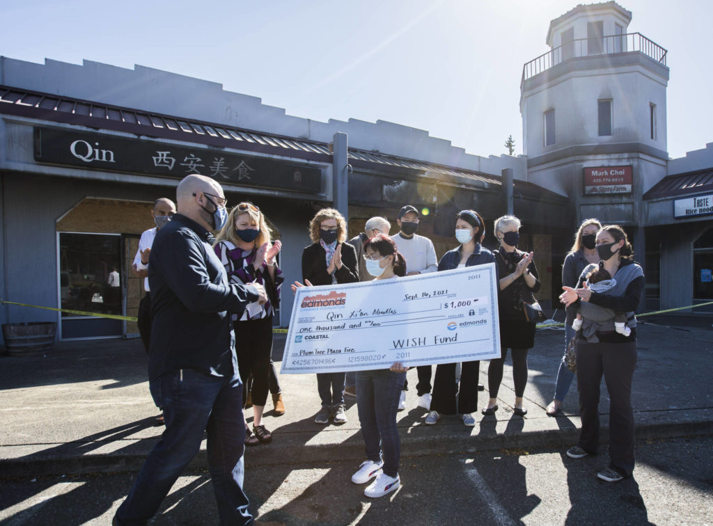 Bufeng Gao, owner of Qin Xi'an Noodles, receives a check Thursday from the Edmonds Chamber Foundation's Wish Fund outside of her restaurant that was burned in a fire. (Olivia Vanni / The Herald)