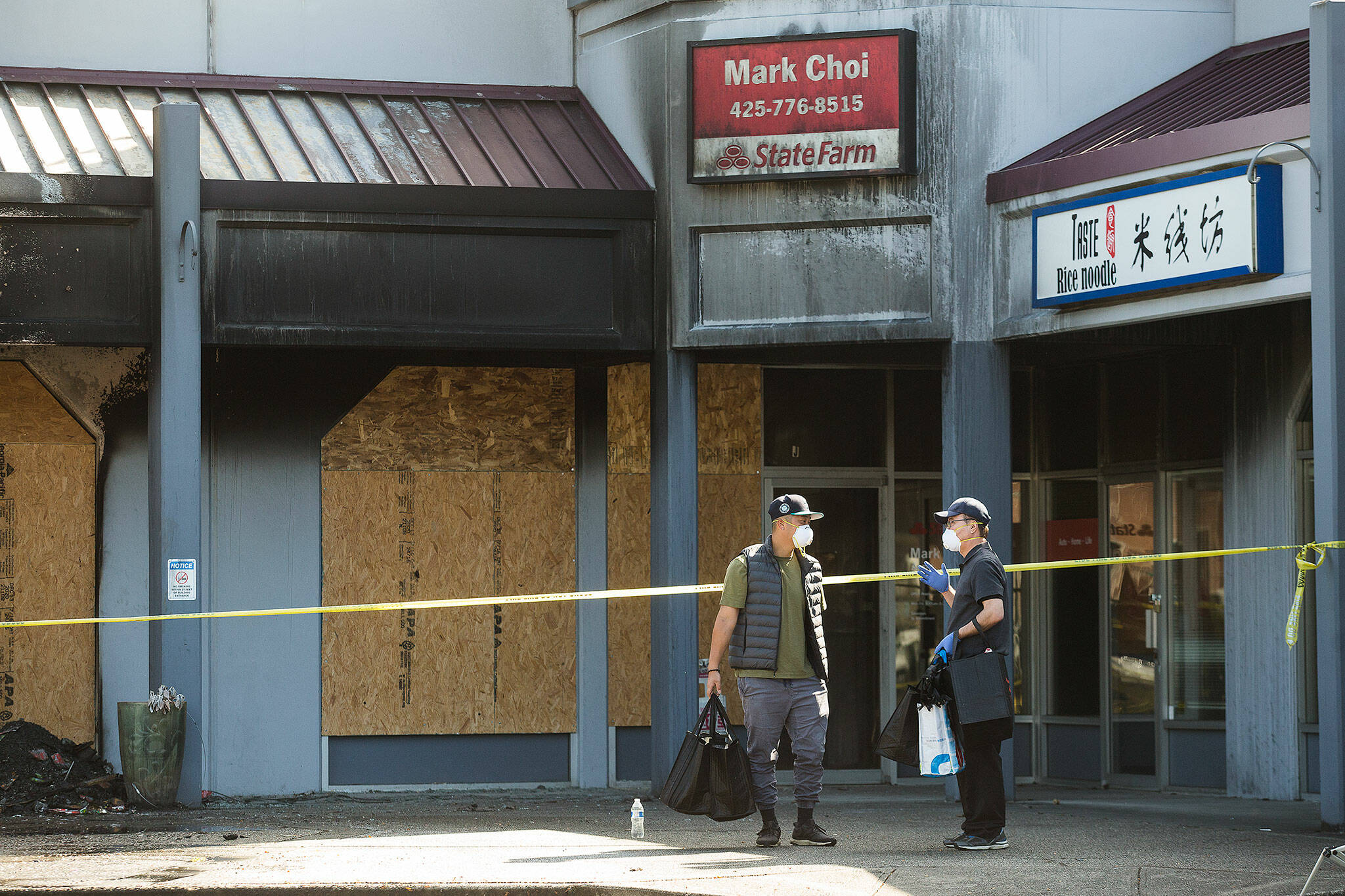 Mark Choi (right) and an employee leave his office in the Plum Tree Plaza after firefighters checked for hot spots on Monday in Edmonds. (Andy Bronson / The Herald)