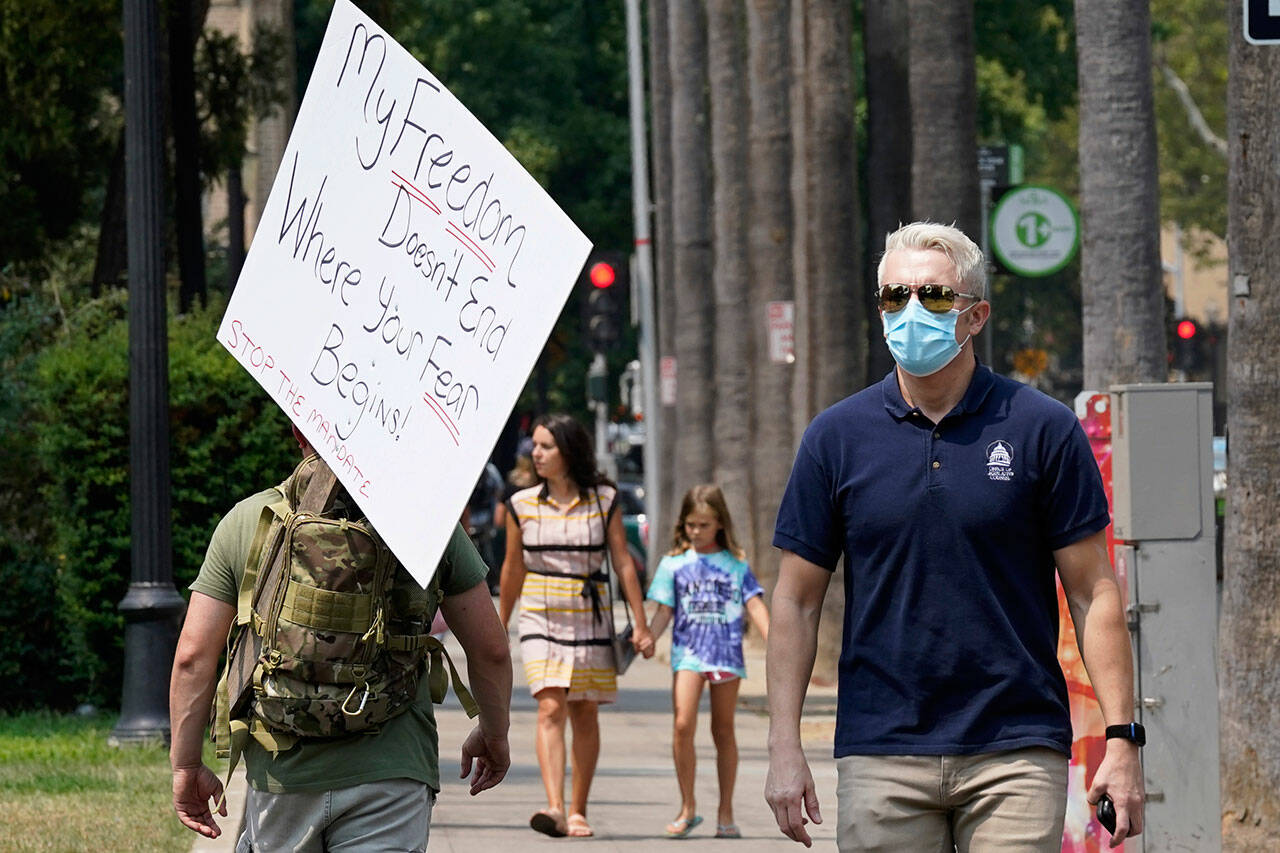 A person toting a sign from a demonstration against mandatory vaccinations passes a man wearing a face mask by the Capitol in Sacramento, Calif. Across the country, anti-vaccine and anti-mask demonstrations are taking scary and violent turns, and educators, medical professionals and public figures have been stunned at the level at which they have been vilified for even stating their opinion. (Rich Pedroncelli / Associated Press file)