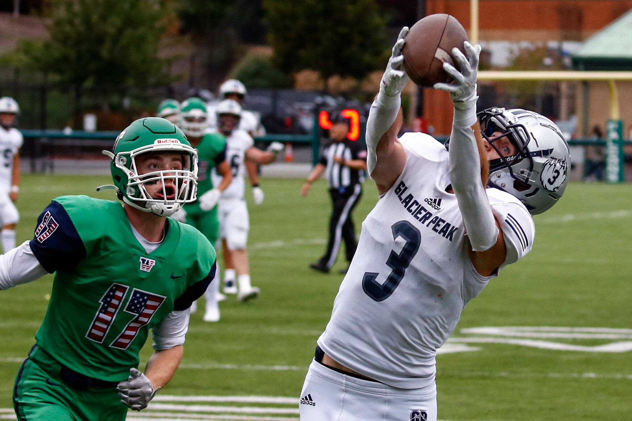 Glacier Peak's Ashton Olson makes a touchdown reception with Woodinville's Jeffrey Perran trailing during a game Thursday evening at Pop Keeney Stadium in Bothell. (Kevin Clark / The Herald)