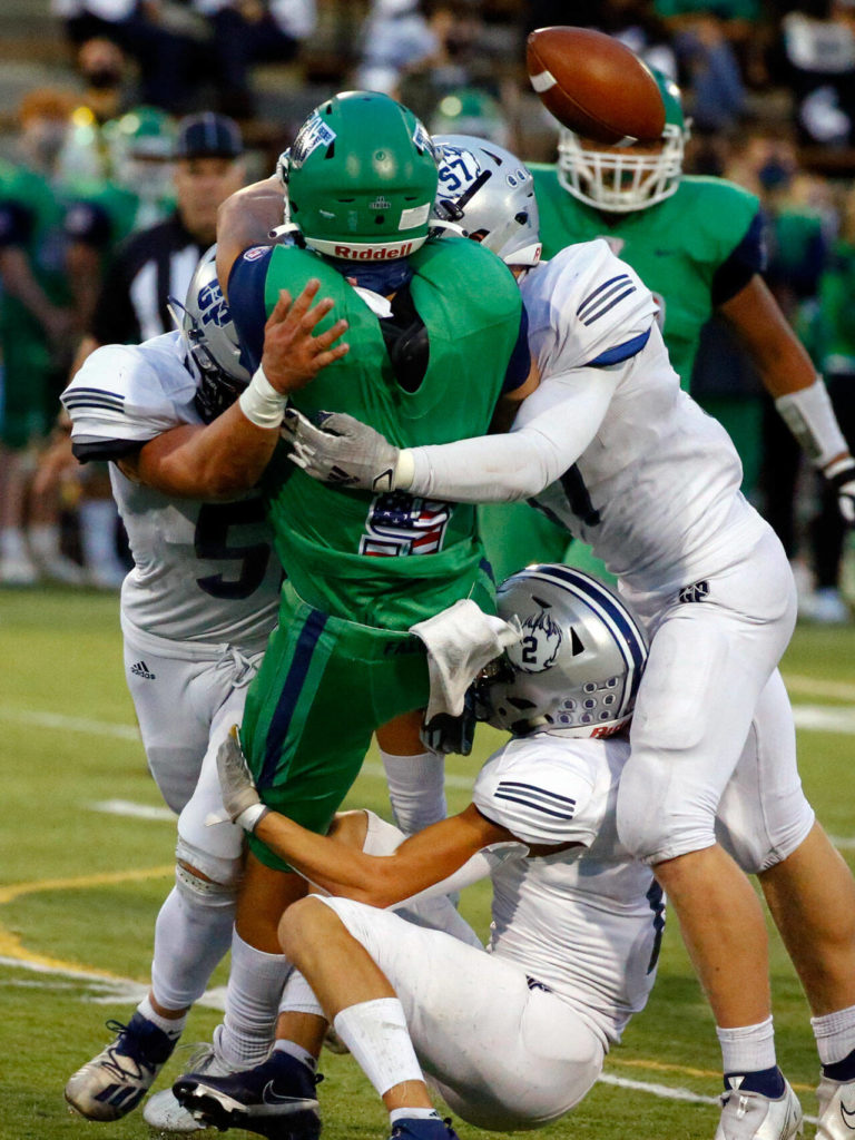 Glacier Peak's defense pressures Woodinville's Theo Grothen forcing an incomplete pass Thursday evening at Pop Keeney Stadium in Bothell on September 16, 2021. (Kevin Clark / The Herald)