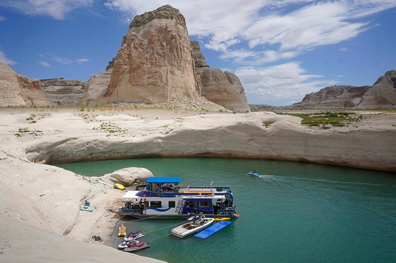 A houseboat rests in a cove at Lake Powell, July 30, near Page, Ariz. This summer, lake and river water levels hit a historic low amid a climate change-fueled megadrought engulfing the U.S. West. (Rick Bowmer / Associated Press)