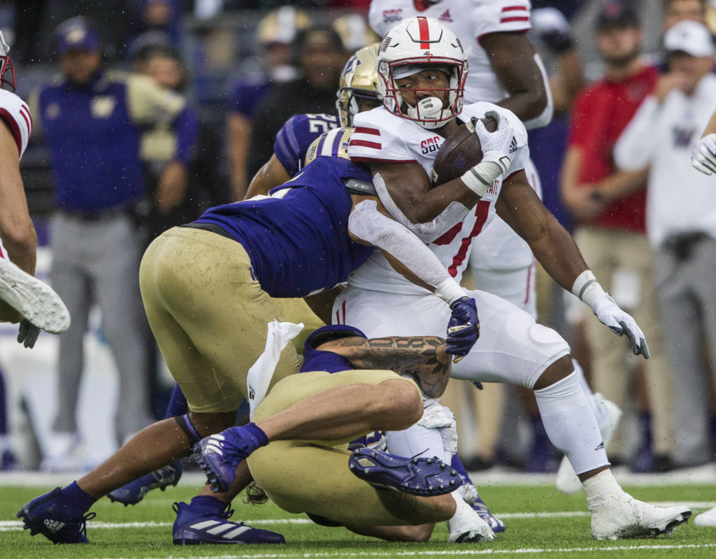 Arkansas State's Alan Lamar is tackled by Washington Huskies defensive back Asa Turner and defensive lineman Tuli Letuligasenoa during the game against Arkansas State on Saturday, Sept. 18, 2021 in Seattle, Wa. (Olivia Vanni / The Herald)