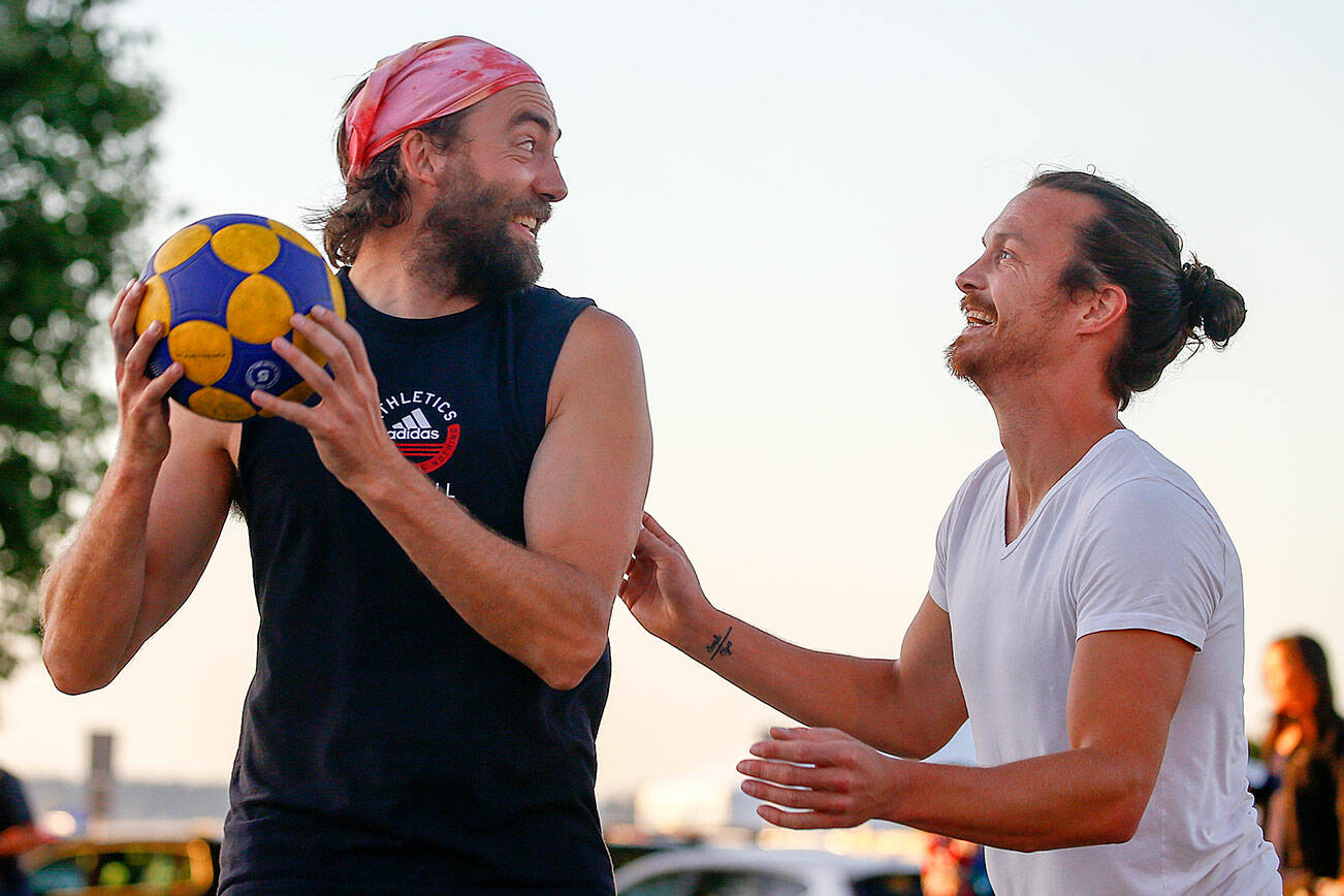 Bill Johnson, left, looks to pass with Sean Hermis defending while playing korfball Thursday evening at Mukilteo Beach on September 9, 2021. (Kevin Clark / The Herald)