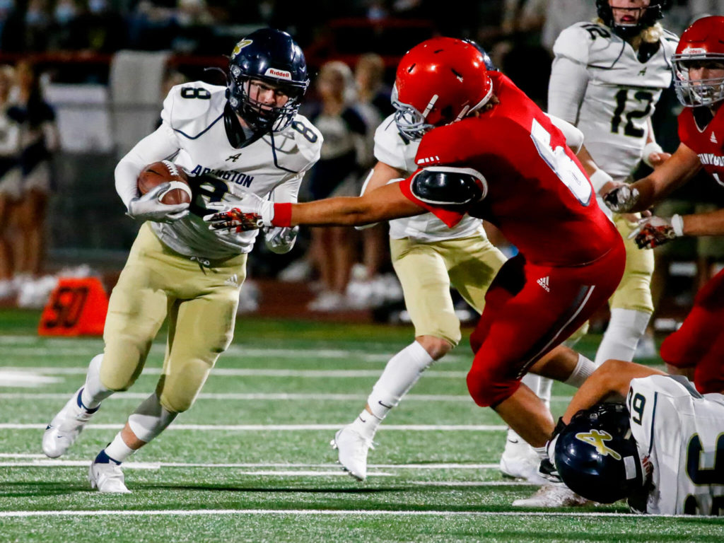 Arlington's RJ Gese rushes with Stanwood's Michael Mascotti closing during the Stilly Cup on Friday night at Stanwood High School. (Kevin Clark / The Herald)