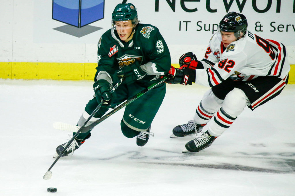 Everett's Ben Hemmerling controls the puck with Portland's O'Brien Jack trailing in the second period Friday night at the Angel of the Winds Arena in Everett on October 8, 2021. (Kevin Clark / The Herald)