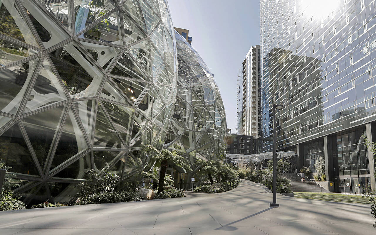 In this March 2020 photo, the Amazon campus outside the company headquarters in Seattle sits nearly deserted. The company will allow many tech and corporate workers to continue working remotely indefinitely, as long as they can commute to the office when necessary. (AP Photo/Elaine Thompson, File)