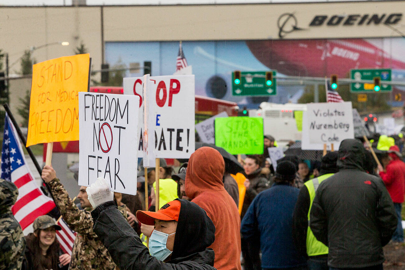 People hold signs in protest of the vaccine mandate after Boeing announced it would terminate workers who do not comply on Friday, Oct. 15, 2021 in Everett, Wa. (Olivia Vanni / The Herald)