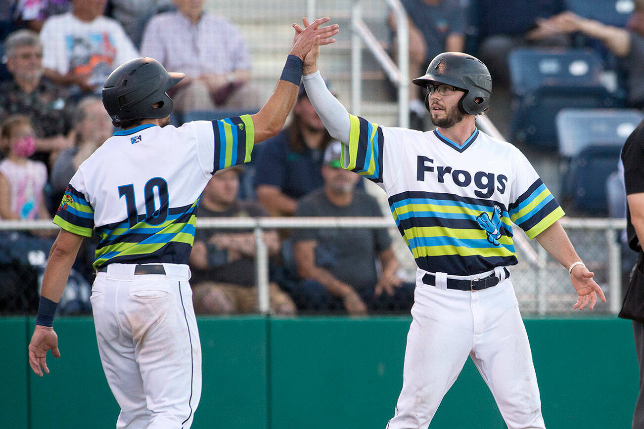 Aquasox's Jake Anchia, left, and Connor Hoover high five after Hoover crosses the plate to score as the Everett Aquasox beat the Vancouver Canadians 11-6 at Funko Field on Tuesday, Aug. 10, 2021 in Everett, Washington.  (Andy Bronson / The Herald)