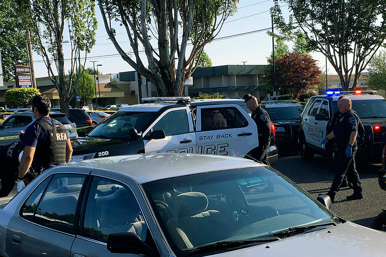 """In this May 31, 2019, photo provided by the Auburn Police Department via the Port of Seattle Police Department, Auburn police Officer Jeff Nelson, second from right, is shown at the scene where he shot and killed Jesse Sarey in a grocery store parking lot in Auburn, Wash. Although Nelson has been investigated in more than 60 use-of-force cases since 2012, he wasn't placed on the King County Prosecuting Attorney's """"potential impeachment disclosure"""" list, or Brady List, which flags officers whose credibility is in question due to misconduct, until after he was charged in Sarey's killing. (Auburn Police Department via Port of Seattle Police Department via AP)"""