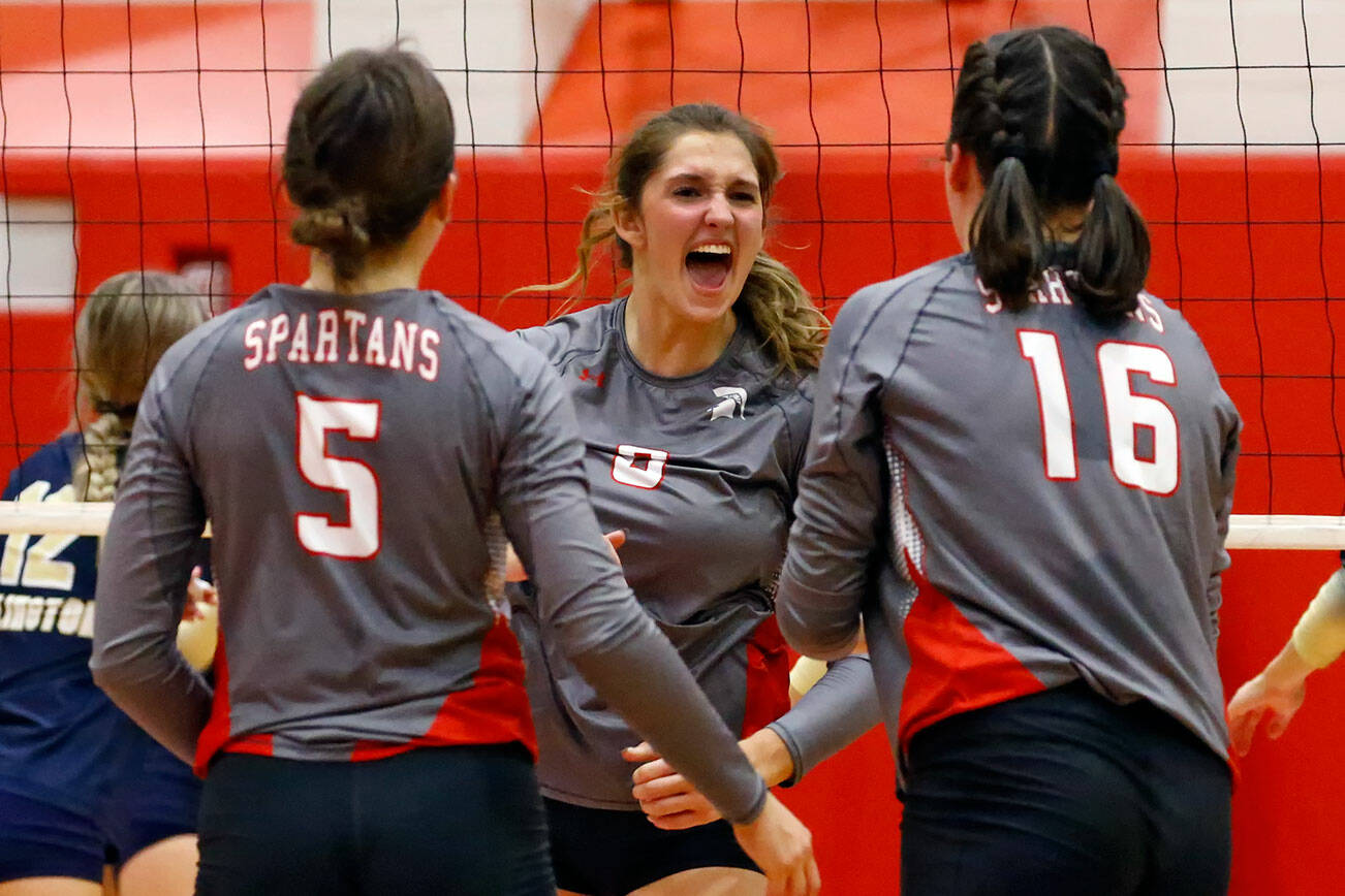 Stanwood's Baylor Hezel, left to right, Olivia Rueckert and Grace Henken celebrate a point against Arlington Thursday night at Stanwood High School on October 21, 2021.  (Kevin Clark / The Herald)