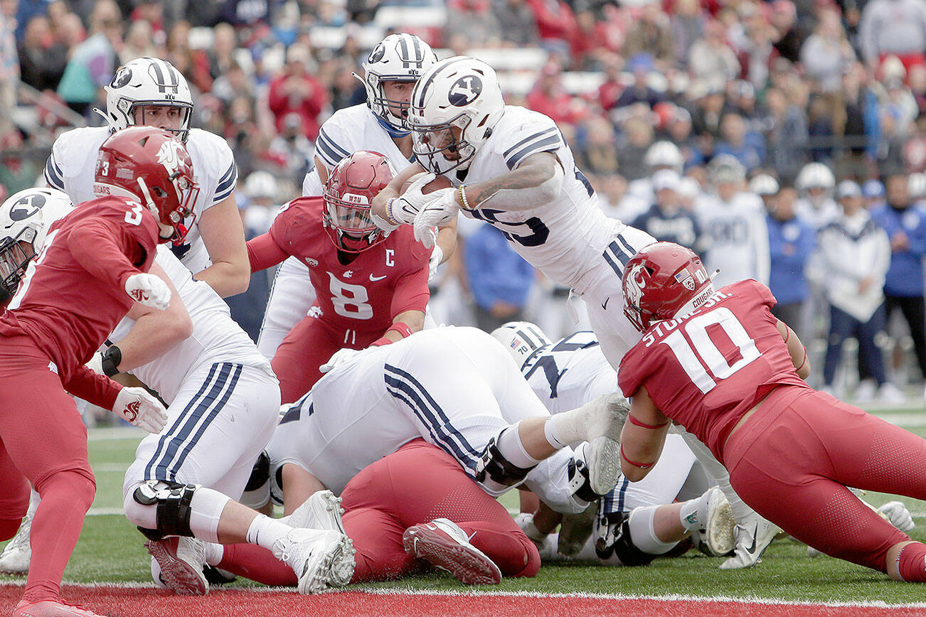 BYU running back Tyler Allgeier, top center, reaches for a touchdown during the second half of an NCAA college football game against Washington State, Saturday, Oct. 23, 2021, in Pullman, Wash. BYU won 21-19. (AP Photo/Young Kwak)